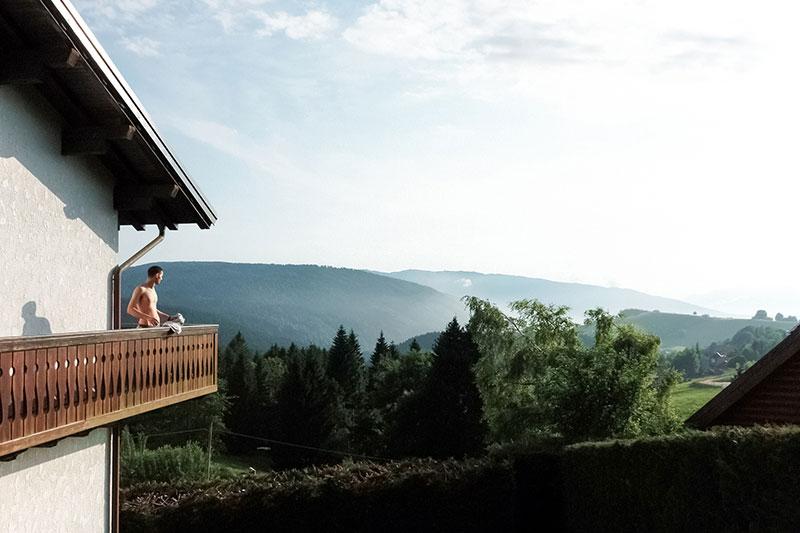 Ragazzo affacciato in terrazza di montagna